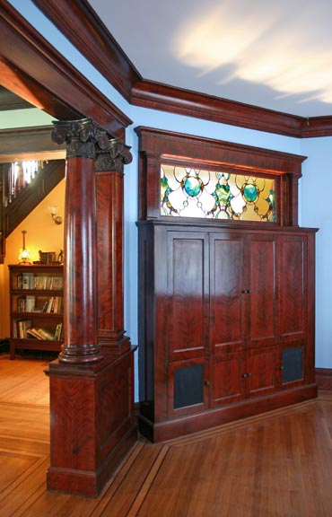 A custom, built-in TV cabinet was created to reclaim a space where a wall was long-ago removed.
