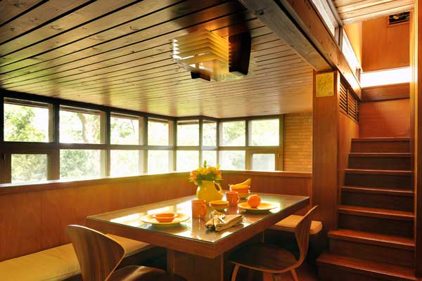 A dining banquette is built into the kitchen balcony. The light fixture is original.