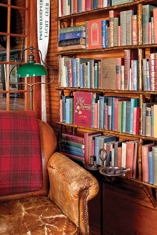 A downstairs room is furnished with vintage leather club chairs and birch-branch shelves overflowing with bound books of the Victorian age.