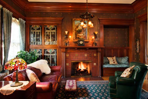 A glass cabinet and a nook create symmetry around the fireplace in the den. Fireplace tiles depict the Mayflower, Monticello, and tribal hieroglyphics.