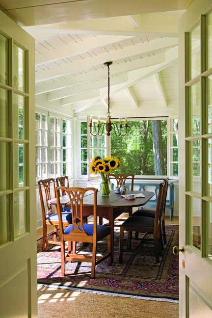 A glassed-in dining porch off the kitchen transforms into a screened porch during warmer weather.