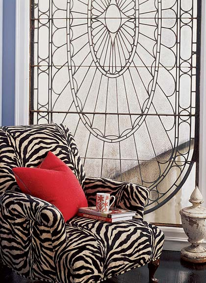 A leaded-glass window from Argentina allows light from the staircase into the master bedroom. Grandmother's easy chair was reupholstered in zebra-print velvet.