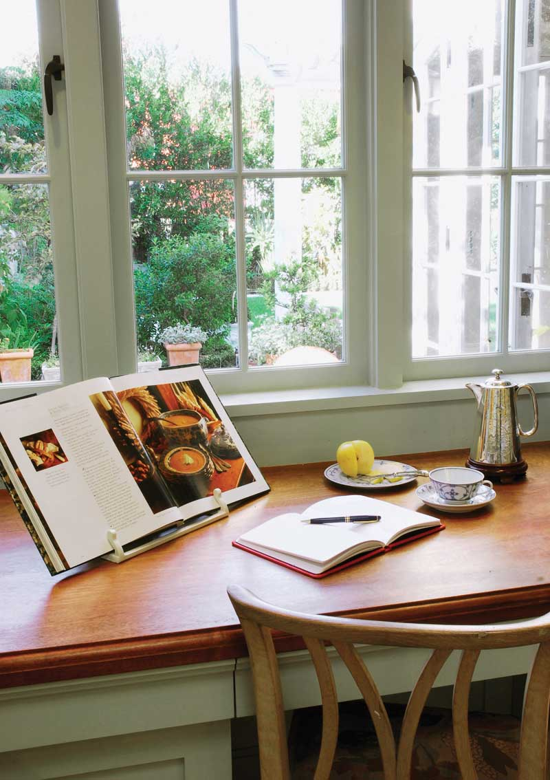 A mahogany desktop and cookbook shelves occupy a shallow nook with views to the garden.