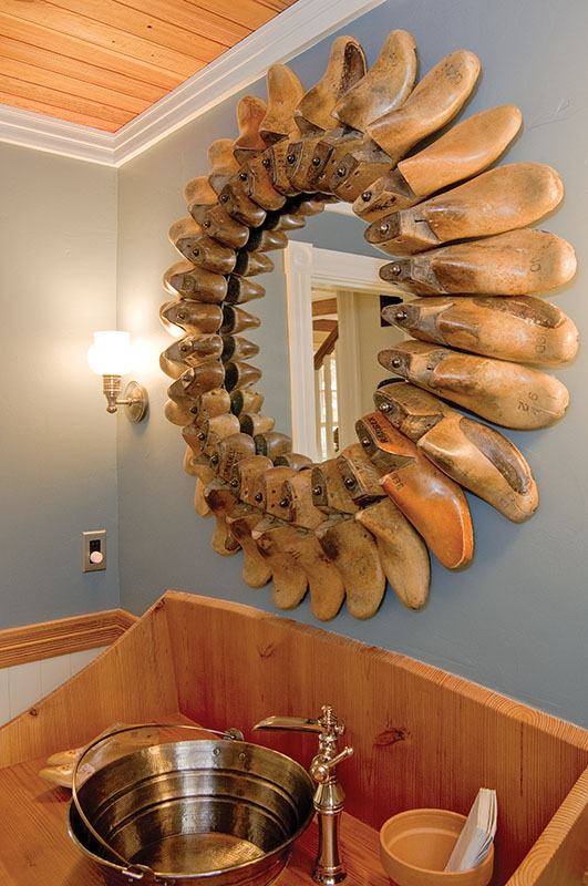 A mirror framed by antique shoe forms.