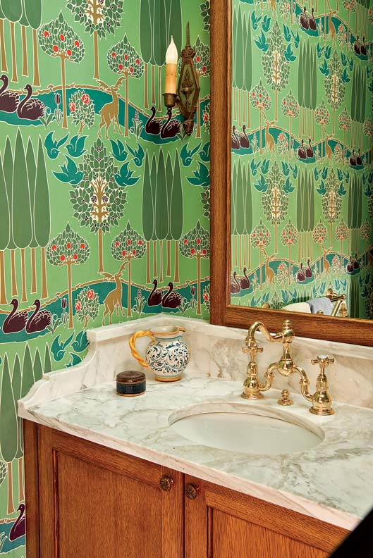 A modest powder room was made to feel larger with the addition of a solid, Victorian-inspired built-in vanity and a mirror that travels all the way to the ceiling. Reproduction Voysey wallpaper adds a whimsical touch.