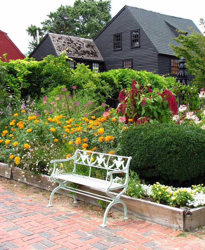 A neoclassical bench is a formal element in the garden at The House of the Seven Gables in Salem, Massachusetts, which features plank-edged raised beds. (Photo: Georgene Bramlage)