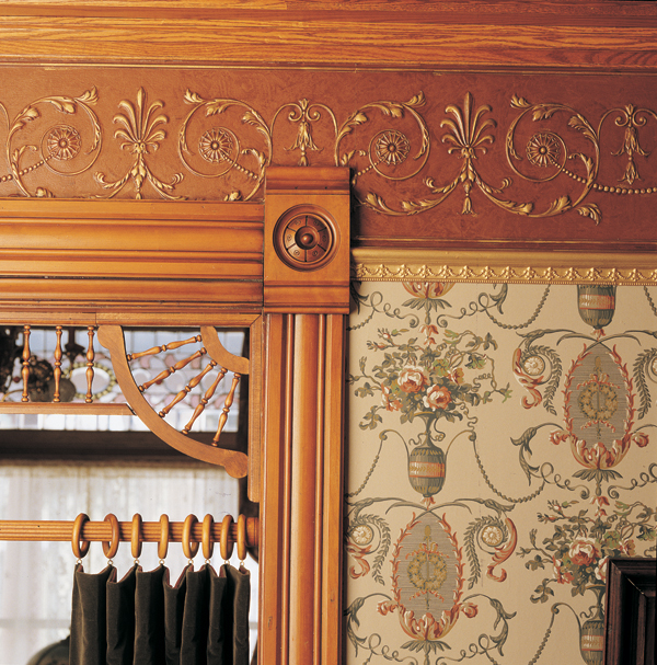 A neoclassical frieze hung over cherry woodwork is made of embossed Lincrusta.