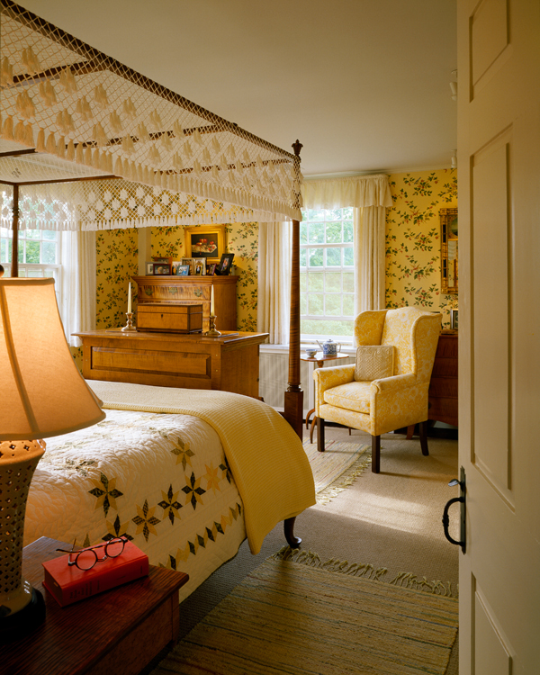 A netted canopy on the four-poster bed and revival wallpaper from Schumacher show Colonial Revival sentiment in the master bedroom.