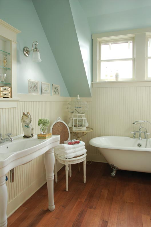 A reproduction tub and sink are flanked by beadboard in the master bath.