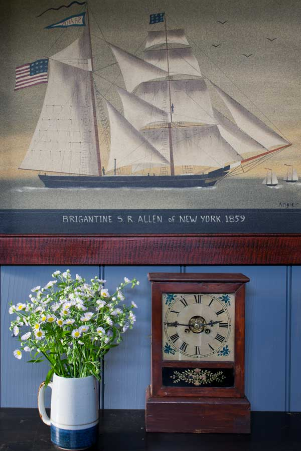 A ship painting by Hope Angier hangs over a modified schoolmaster's desk in the living room.
