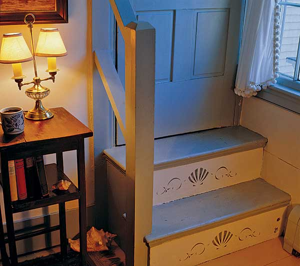 A simple anthemion pattern from Liberty Design Co. decorates the risers of a closed stair, a subtle use of stenciling.