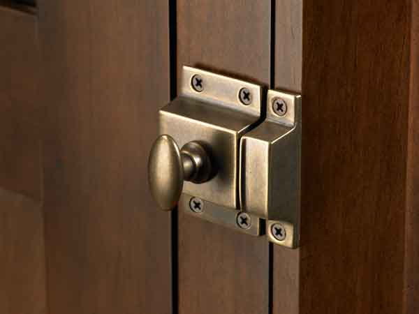 A simple cabinet latch from Top Knobs has a patinated finish for an aged look.