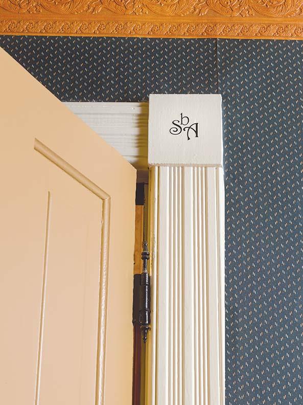A stenciled SbA monogram decorates corner blocks on the bedroom trim.