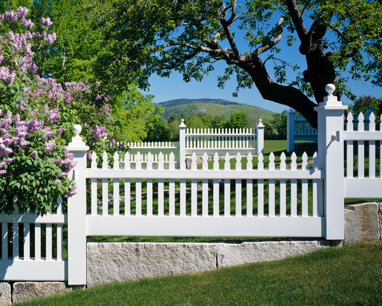 A stepped, Federal-style picket fence on granite plinths graces the picturesque property.