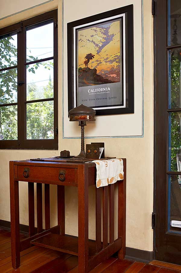 "A Stickley Bros. table holds an Old Mission Kopper Kraft desk lamp and a rare copper desk set by Forest Craft Guild. The reproduction train poster advertises ""America's Vacation Land."""