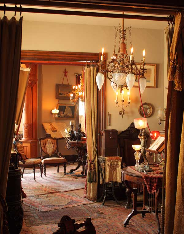 A view from the back parlor hints at the collection of Victorian antiques. A lamp on the center table below is connected, in the Victorian fashion, to the gasolier above by a rubber hose.