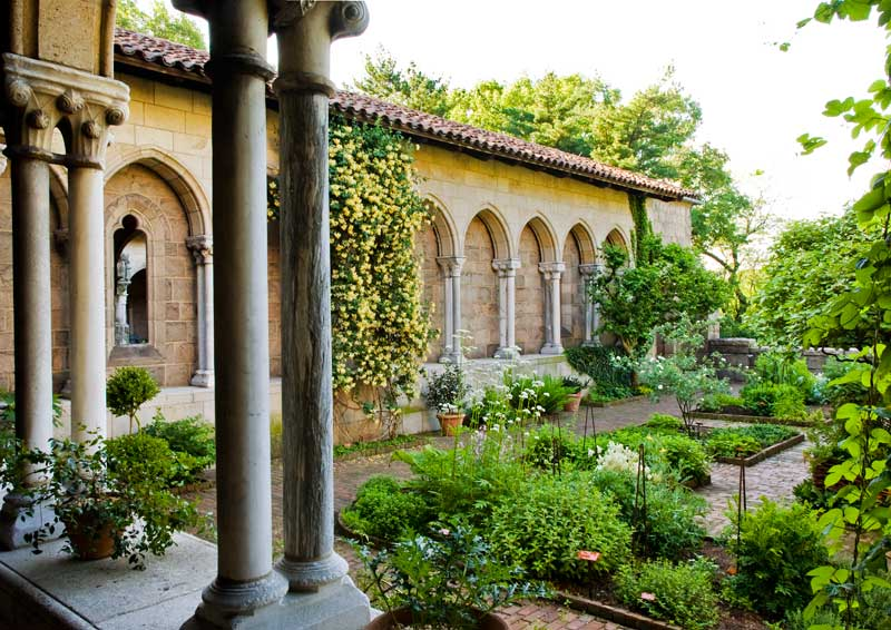 A view into Bonnefont Cloister herb garden, where vertical elements enhance the sense of enclosure. The honeysuckle on the blind arcade is 'Graham Thomas.'