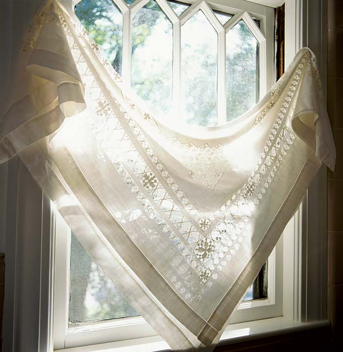 A vintage lace tablecloth, draped diagonally, is a simple but dramatic window treatment.