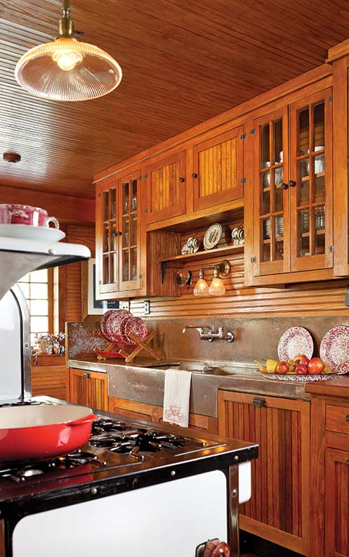 The large kitchen is relatively new. Its rambling layout, well-matched fir beadboard, vintage stove, and copper sink make it look original.