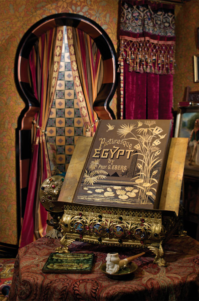 A bookstand is the sine qua non for a library, as with this elaborate, bejeweled and gilded metal stand ca. 1880, which displays an equally ornate volume on the mysteries of Egypt, and sits appropriately in an early-20th-century Turkish room. (Photo: William Wright)