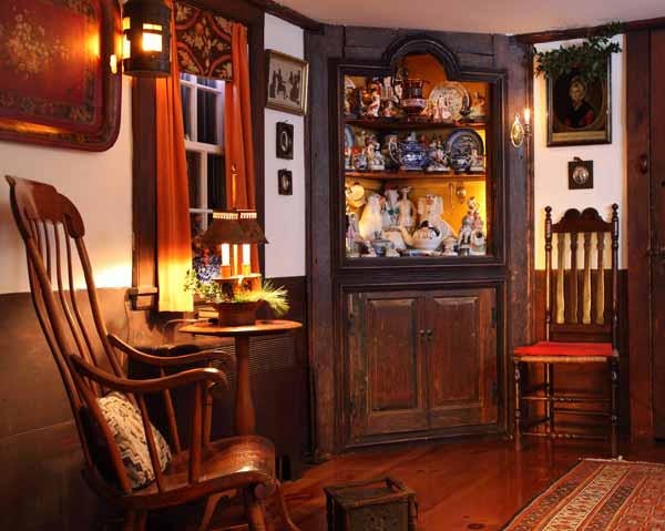 Amidst mostly English furniture, two American chairs flank the corner cupboard made from reclaimed wood. The rocker dates to ca. 1820. At right is a Gothic chair from New England.
