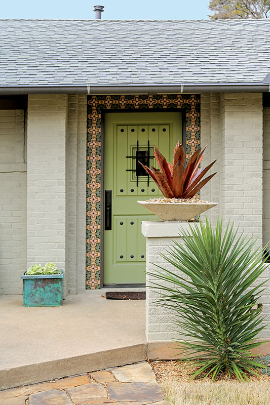 An arresting front door is bordered in tile.