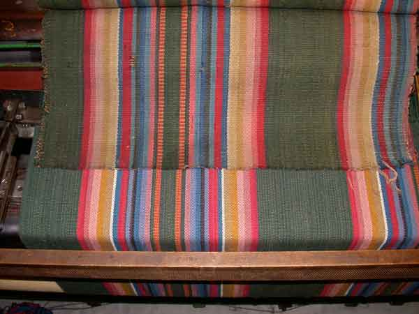 An original Venetian striped carpet (on top) with its wool reproduction (still on the loom) for the 1825 Beall-Stibbs House in Wooster, Ohio. By Thistle Hill Weavers