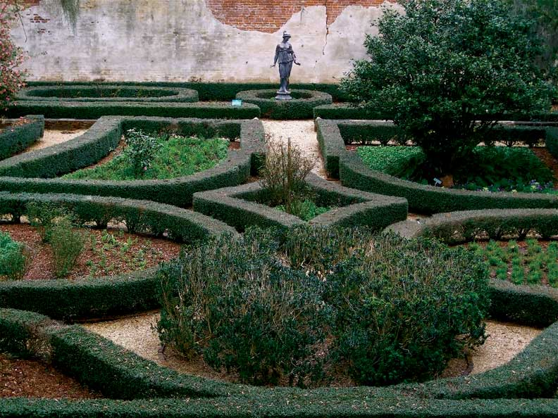 Architectural elements such as a brick wall and statue add focal points to the geometric precision of the gardens at Rosedown Plantation.