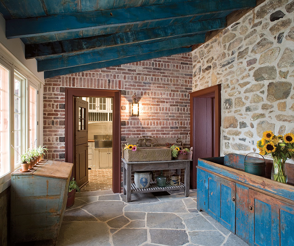 A newly enclosed porch connects old and new house parts. An old stone sink and painted grain bin are part of the patina of the old house. The ceiling was painted to match the bin.