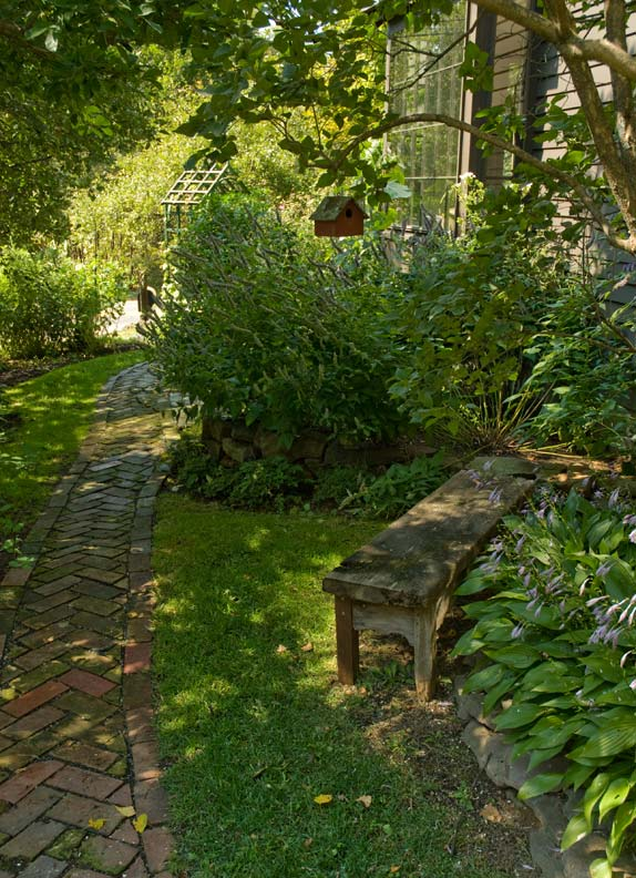 At the front of the property, a herringbone brick path connects garden and house.