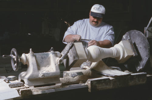 Working on a horizontal lathe, Dean Littleton transforms a rectangular blank of Texas limestone into a round cylinder.