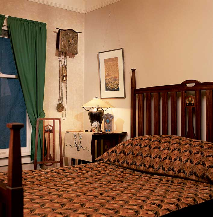 A guest bedroom is furnished with an elegant, five-piece mahogany suite made in 1904 by the Luce Furniture Co. of Grand Rapids, Michigan, in the Glasgow style. The brass wall clock is also in the Glasgow style.