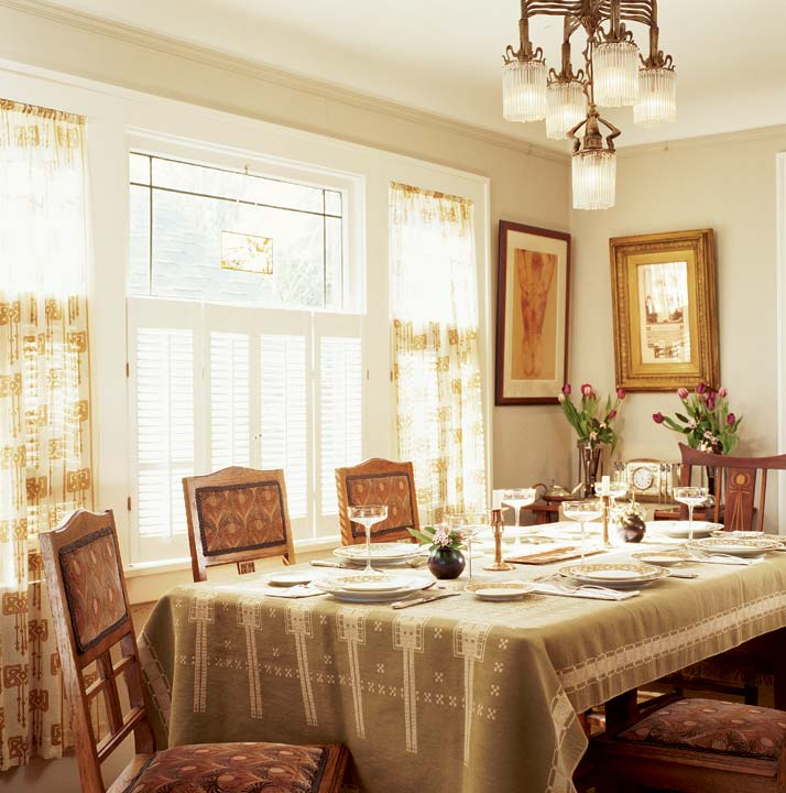 A German Secessionperiod cloth covers the table set with Secession enameled stemware by the Austrian firm Theresienthaler; English walnut chairs are covered in a modern peacock feather-pattern velvet.