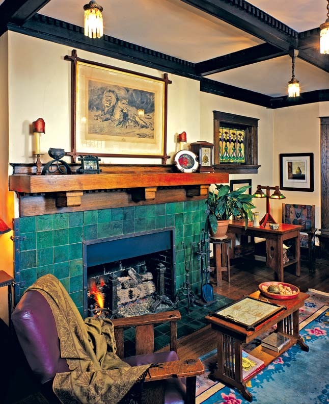 Stunning green tile accented by riveted iron straps makes the fireplace the centerpiece of the room in this Memphis bungalow. It's hard to believe a previous owner had painted the entire thing red.