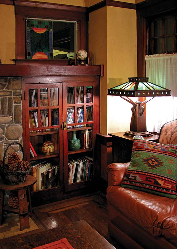 An antique Arts & Crafts table lamp, purchased on eBay by the homeowner, echoes the rich woodwork of built-in bookcases.