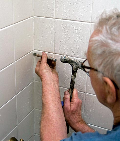 Riley removes old grout with a small X-acto knofe and a hammer.