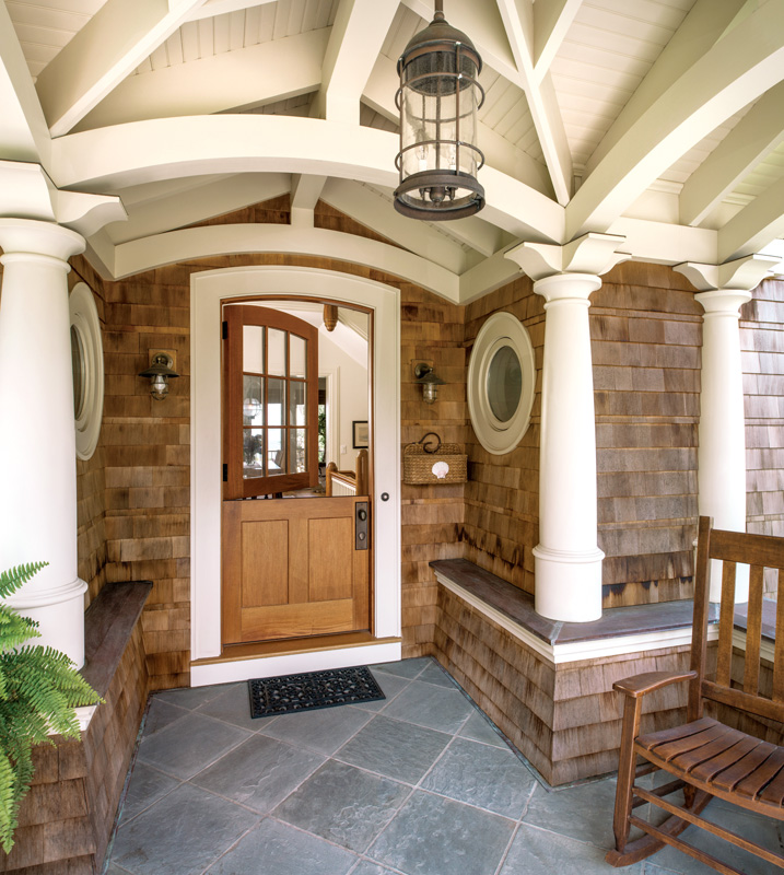 Visitors are greeted by a front porch. Classically inspired Tuscan-style columns with elegant brackets support the roof. Opposite: The stone fireplace is a central feature of the light-filled living area. Traditional beams divide the beadboard ceiling.
