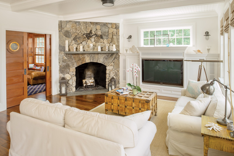 The stone fireplace is a central feature of the light-filled living area. Traditional beams divide the beadboard ceiling.