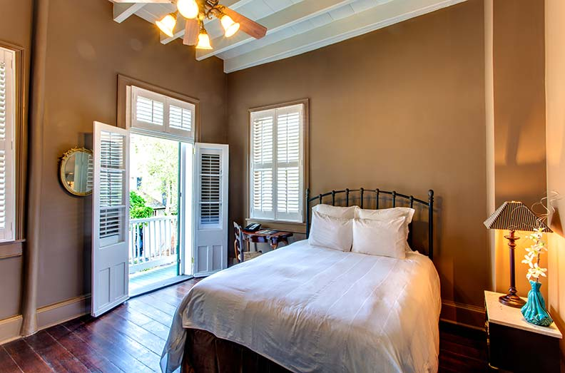 In the two-story Cottage 4, a bedroom opens up to a balcony overlooking the courtyard.