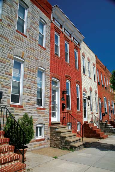 Two Baltimore traditions side by side: a workman's brick row house amid Formstone-covered neighbors.