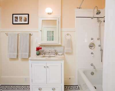 Modern amenities—like a shower with thermostatic controls and adjustable-height hand sprayer—blend in with the bathroom's original marble sink (and reproduction bridge faucet) thanks to carefully matched fixtures that create a warm, period feel.