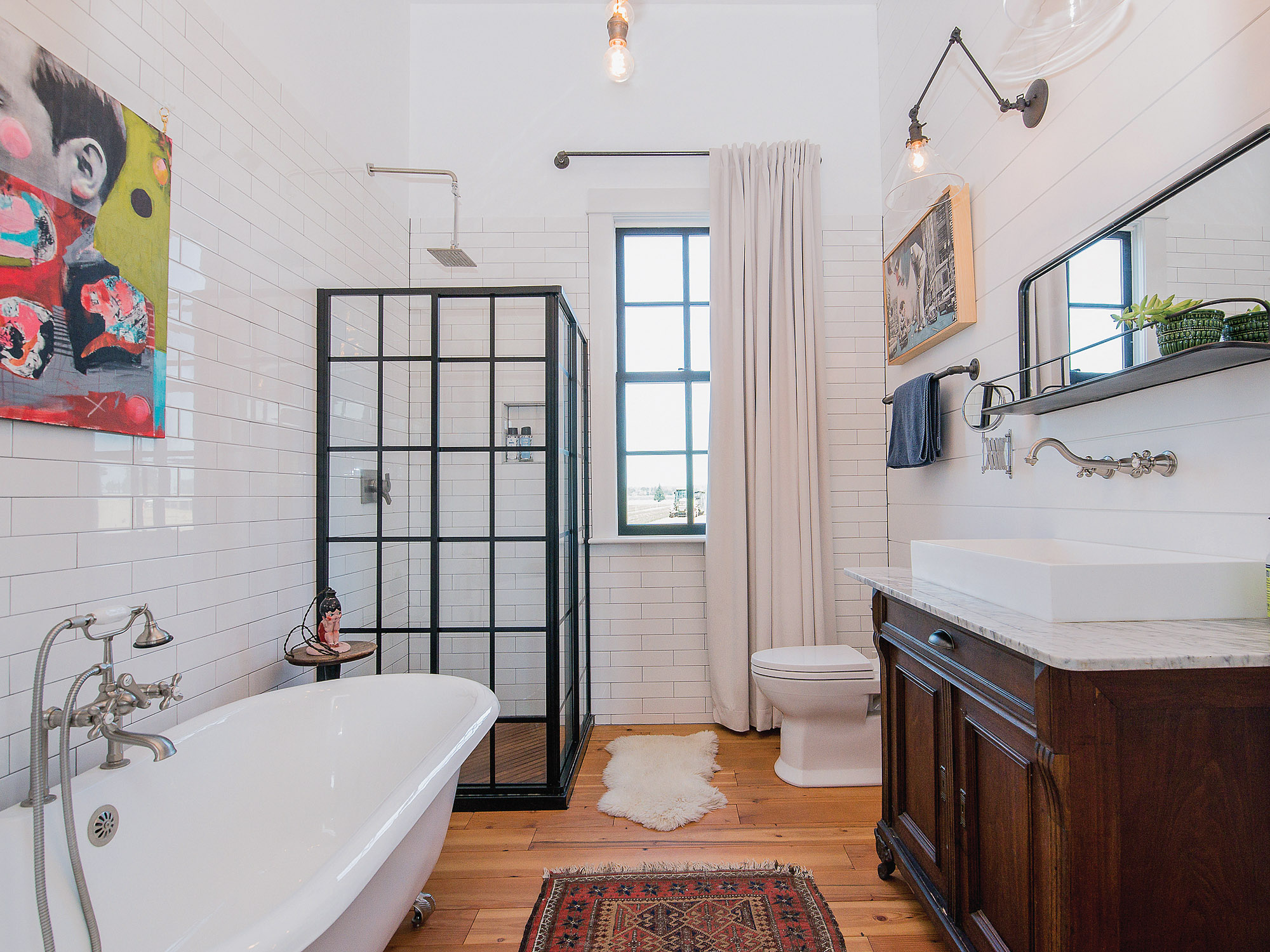 With a converted antique dresser and old-fashioned tub complementing industrial touches, the new bath is retro-chic.