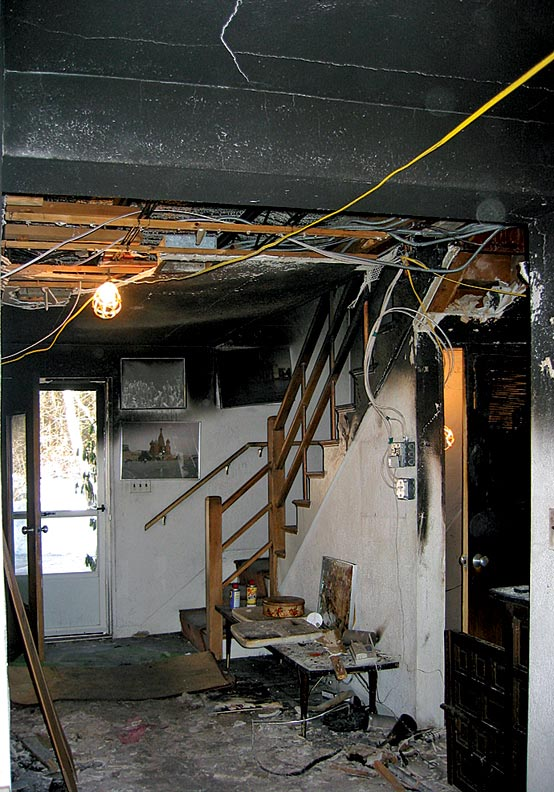 Flames spread from the den into the entry hall, charring the top half of the stairs.
