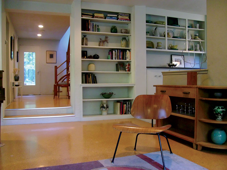 The living room's original built-in shelves were retained, and the concrete slab was topped with a floating cork floor.
