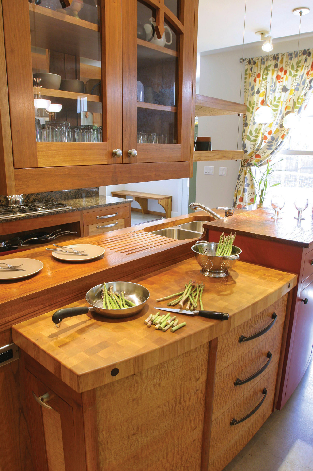 An end-grain butcher-block work station alongside a face-grain drainboard countertop, both made by DeVos Woodworking.