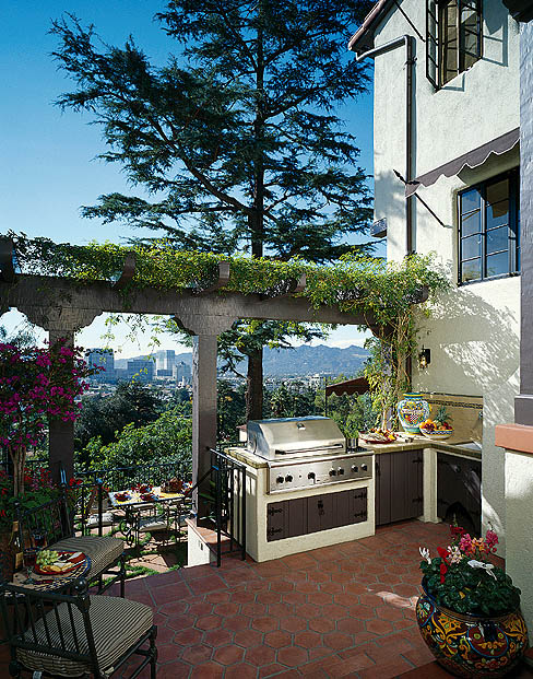 Because the yard is so steeply terraced, David Lans designed this patio to take advantage of the wonderful views and to create a link between the indoors and outdoors, a place for the family to enjoy the mild Southern California climate and entertain informally. The outdoor grill by Thermador makes outdoor cooking as easy and convenient as it is in the kitchen.