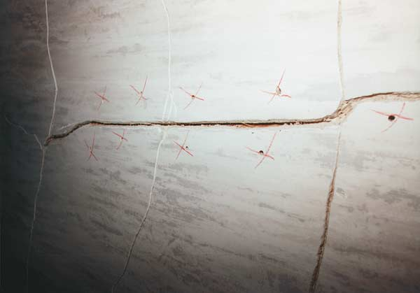 Because this plaster was becoming detached from the lath (delaminated), it has been marked for reattachment. The crack is notched and ready to be vacuumed out. (Photo: The Lords)