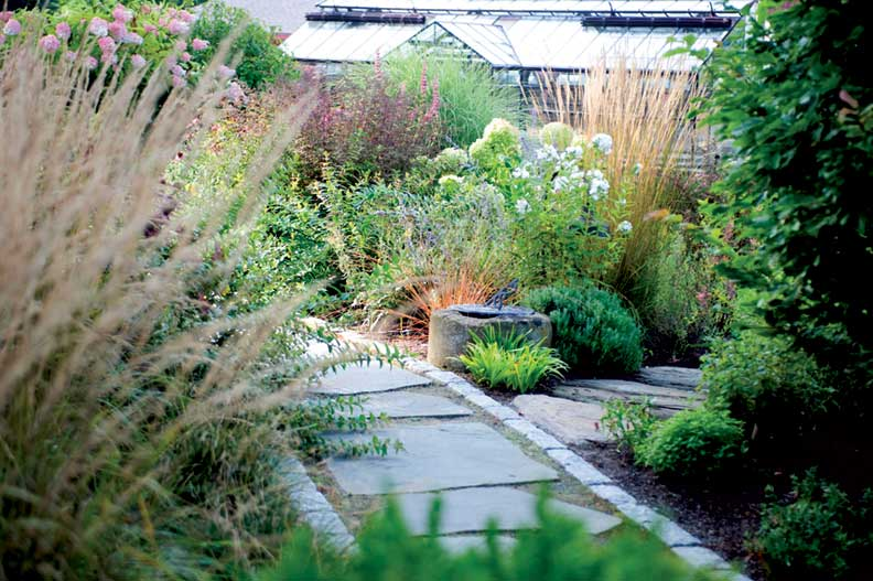 Along a winding garden walk, a haze of soft color helps to obscure the greenhouse.