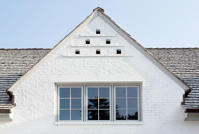 Architect James Collins chose a brick façade with wood shingles and casement windows.
