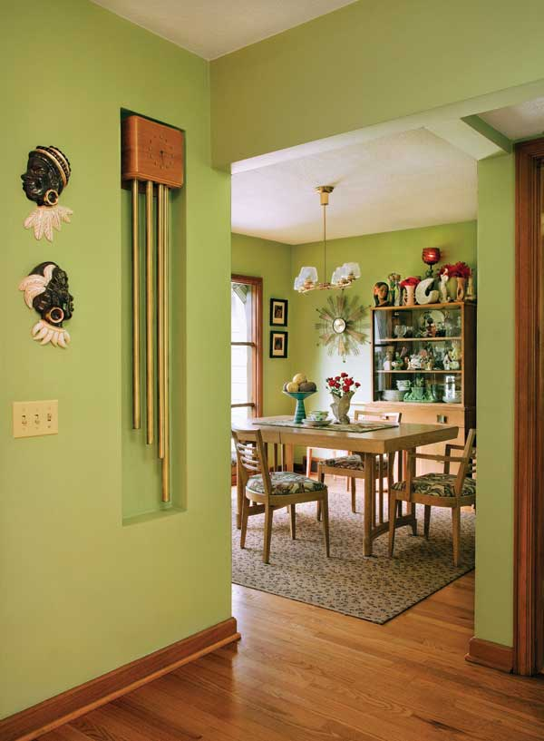 Beyond the doorbell in the foyer is the dining room, with its 1940s lime-green walls and blonde furniture.